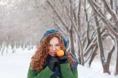 Girl holds mandarin at winter day Stock Image