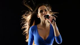 Girl holds a microphone and sings lyrical songs. Black background stock video