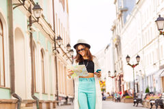 Girl holds mobile phone and city map on the street Royalty Free Stock Image