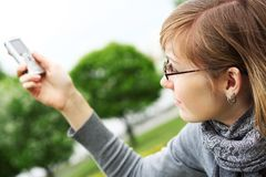 The girl holds a mobile phone in hands Royalty Free Stock Images