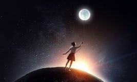 Girl holds the moon . Mixed media stock photos