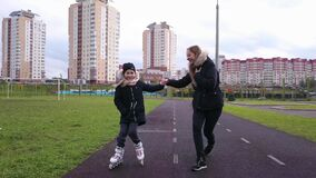 Girl holds mother`s hand and trying skating rollers.
