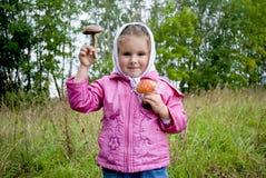 The girl holds mushrooms in hands. The girl holds two mushrooms in hands: a fly agaric and a birch mushroom Stock Images
