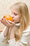 Girl holds an orange Stock Images