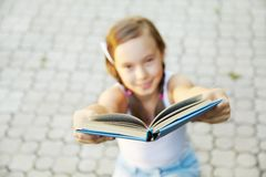 Girl holds out a book Stock Photography