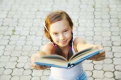 Girl holds out a book Stock Photo