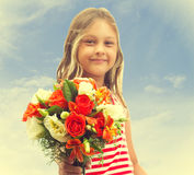 Girl holds out a bouquet of flowers Royalty Free Stock Photography