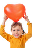 Girl holds over head heart shape balloon. Laughing little girl holds over her head heart shape balloon isolated on white background Royalty Free Stock Image