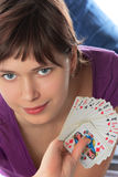 Girl holds a pack of playing cards Royalty Free Stock Image