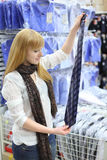 Girl holds packed tie in shop Royalty Free Stock Photo