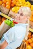 Girl holds packet with fresh vegetables Stock Photos