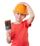 Girl holds the paintbrush. Girl in a protective helmet holds the paintbrush Stock Image
