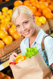 Girl holds paper bag with fresh vegetables Stock Photography
