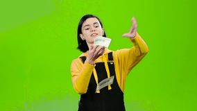 Girl holds paper bills in her hands and rejoices in victory. Green screen. Slow motion. Teenage girl holds paper bills in her hands and rejoices at the victory stock video