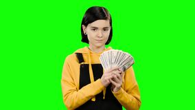 Girl holds paper bills in her hands and rejoices in victory. Green screen. Teenage girl holds paper bills in her hands and rejoices at the victory, she is lucky stock video
