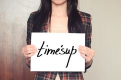 Girl holds a paper sheet with slogan time is up against harassment. And sexual discrimination Royalty Free Stock Images