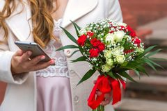 The girl holds a phone in her hand, a bouquet in her other hand stock photography