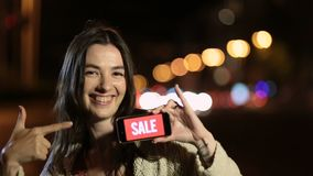 Girl holds phone with sale ad on screen at night stock video