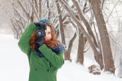 Girl holds photographs by retro camera at winter day Royalty Free Stock Photo