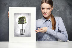 Girl holds a picture of. Girl holds a frame with the image of Eco concept, green tree growing in a bulb Royalty Free Stock Images