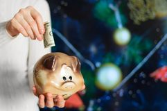 Girl holds a piggy bank in her hands and puts a dollar in it. On the background of the Christmas tree royalty free stock photo