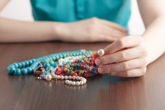 Girl holds a pile of jewelry Royalty Free Stock Photography