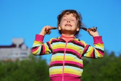 Girl holds plaits and has closed eyes Stock Images
