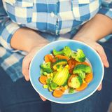 The girl holds a plate with vegetables. Healthy eating concept. A girl in jeans and a plaid shirt. Casual Style. Proper nutrition. Diet. Health. Vegetarian Royalty Free Stock Photography
