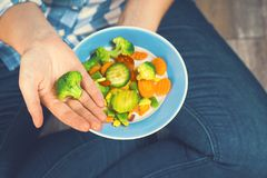 The girl holds a plate with vegetables. Healthy eating concept. A girl in jeans and a plaid shirt. Casual Style. Proper nutrition. Diet. Health. Vegetarian Stock Photography
