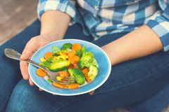 The girl holds a plate with vegetables. Healthy eating concept. A girl in jeans and a plaid shirt. Casual Style. Proper nutrition. Diet. Health. Vegetarian Royalty Free Stock Image