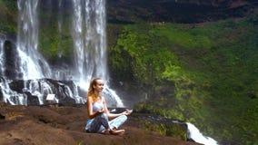 Girl holds pranayama yoga pose on large rock at waterfall