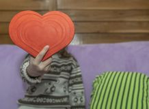 The girl holds red heart in front of her royalty free stock photography