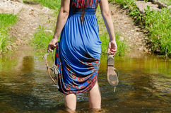 Girl holds sandals wade barefoot flowing stream. Girl holds gray summer sandals and wade barefoot through the fast flowing stream in the park track stock images