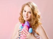 Girl holds shampoos Royalty Free Stock Images