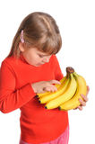 Girl holds a sheaf of bananas on white Royalty Free Stock Photography
