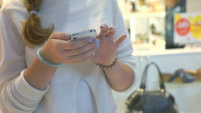 Girl holds silver smartphone. Close-up. Girl holding silver smartphone and reads informational text. Close-up stock video footage