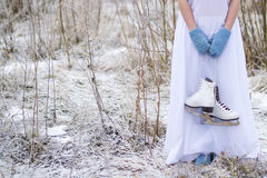 The girl holds the skates for figure skating. The girl keeps the skates for figure skating in a long dress and mittens Stock Photography