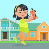 Girl Holds Small Dog in Hands in Front of Houses Royalty Free Stock Photos
