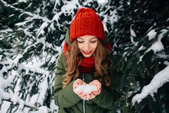 Girl holds snow in hands in winter snowy forest Stock Photo