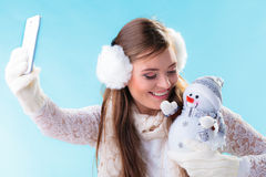 Girl holds snowman toy taking self picture. Royalty Free Stock Images