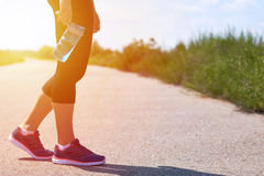 Girl holds sports bottle with water for drinks, legs and sneakers, sunlight Stock Photography