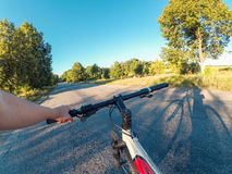 The girl holds the steering wheel with one hand go pro. The girl stands near the bicycle and holds the steering wheel with one hand on an asphalt road in nature royalty free stock image