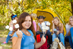 Girl holds sticks with marshmallow near tent Royalty Free Stock Photography