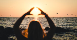 Girl holds sun near the sea at sunset. The sun creates a warm morning, even at cool sea. To keep warm, we sun should touch the sun, taking it into the hands Stock Photo