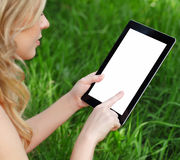 Girl holds a tablet on a background of green grass Stock Photography