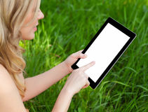 Girl holds a tablet on a background of green grass stock photos