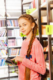 Girl holds tablet near bookshelf in library Royalty Free Stock Images
