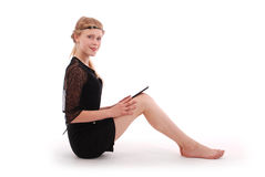 Girl holds tablet pc sitting Royalty Free Stock Image