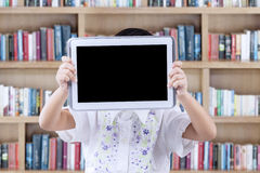 Girl holds tablet to cover her face in library Stock Photo
