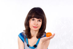 Girl holds a tangerine Royalty Free Stock Images